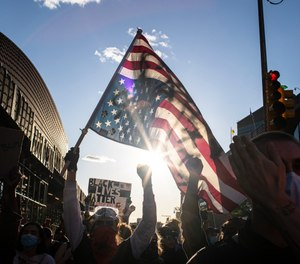 A man holds a U.S. flag upside down, a sign of distress, as protesters march down the street during a solidarity rally for George Floyd, Sunday, May 31, 2020, in the Brooklyn borough of New York. (AP Photo/Wong Maye-E)