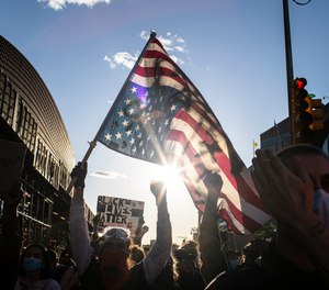 A man holds a U.S. flag upside down, a sign of distress, as protesters march down the street during a solidarity rally for George Floyd, Sunday, May 31, 2020, in the Brooklyn borough of New York.