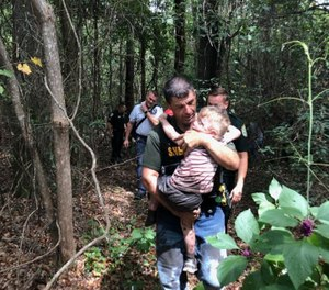 Santa Rosa County Sheriff's Office Deputy Robert Lenzo carries three-year-old Aedric Hughes, who deputies recovered with the help of tracking bloodhounds.  (Photo/Santa Rosa County Sheriff's Office)