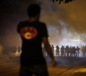 A man watches as police walk through a cloud of smoke during a clash with protesters Wednesday, Aug. 13, 2014, in Ferguson, Mo.