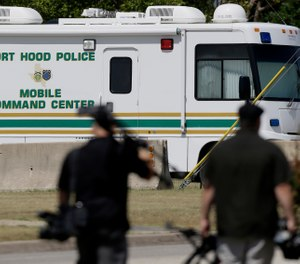 Television cameramen walk by a Fort Hood Police Mobile Command Center near the Lawrence H. WIlliams Judicial Center as a pretrial hearing gets underway, Tuesday, July 9, 2013, in Fort Hood, Texas. (AP Photo/Tony Gutierrez)
