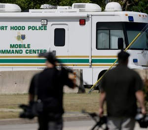 Television cameramen walk by a Fort Hood Police Mobile Command Center near the Lawrence H. WIlliams Judicial Center as a pretrial hearing gets underway, Tuesday, July 9, 2013, in Fort Hood, Texas.