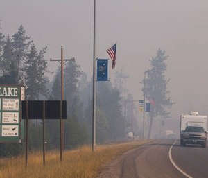 A pickup truck pulls a camper through the wildfire smoke in Seeley Lake in Missoula County, Mont. (Kari Greer/U.S. Forest Service via AP)