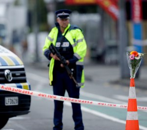 Flower rest at a road block, as a Police officer stands guard near the Linwood mosque, site of one of the mass shootings at two mosques in Christchurch, New Zealand, Saturday, March 16, 2019.