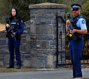 Police officer, left, stands guard with a rose on her chest to pay respect at the burial service for a victim of the Friday March 15 mosque shootings