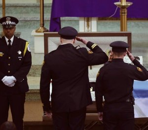 Two officers salute Chicago police Commander Paul Bauer before his funeral mass at Nativity of Our Lord Roman Catholic Church Saturday, Feb. 17, 2017, in Chicago.