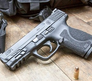 The pistol uses a blackened stainless steel slide and is topped with white painted three-dot sights.
