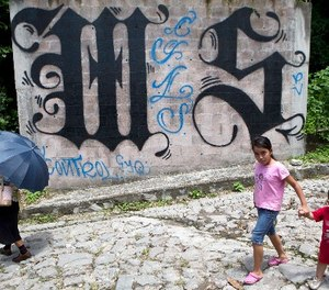In this Aug. 21, 2014 file photo, a family walks by a wall covered by a symbol from the Mara Salvatrucha, of MS-13 gang in Ilopango, El Salvador. (AP Photo/Esteban Felix, File)