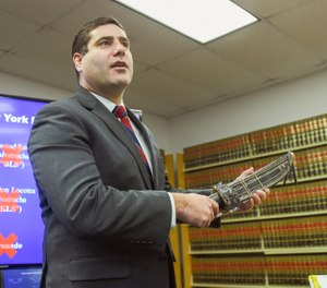 Suffolk County District Attorney Timothy Sini holds a machete while announcing an indictment of nearly 100 MS-13 gang members and associates during a news conference at Suffolk County Court in Riverhead, N.Y., Friday, Dec. 20, 2019. (James Carbone/Newsday via AP)