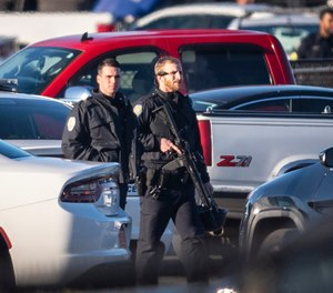 A police officer with the Winston-Salem Police Department walks across the parking lot of the Joycelyn V. Johnson Municipal Services Center after reports of gunshots in Winston-Salem, N.C. early Friday, Dec. 20, 2019. (Andrew Dye/The Winston-Salem Journal via AP)