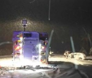 This image taken from a video of the crash scene shows an ambulance on its side after a head-on collision that seriously injured two EMTs. (Image KSTP.com)