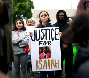 A protester holds a sign at the Edmond Police Department during a protest rally honoring the life of Isaiah Lewis, who was fatally shot in April. (Photo/AP)