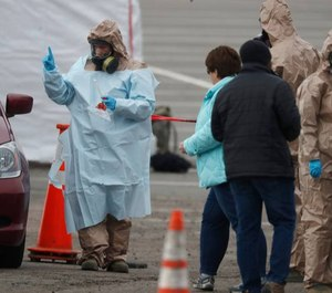 Colorado National Guard medical personnel perform coronavirus tests on a motorist at a drive-through testing site outside the Denver Coliseum. (Photo/AP)