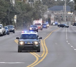 Police cars escort an ambulance after a shooter open fire inside the Pensacola Air Base, Friday, Dec. 6, 2019 in Pensacola, Fla. (Tony Giberson/ Pensacola News Journal via AP)