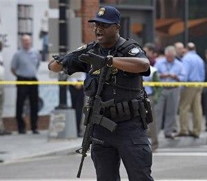 Police tell members of the media to move near the Washington Navy Yard in Washington, Thursday, July 2, 2015. (AP Image)