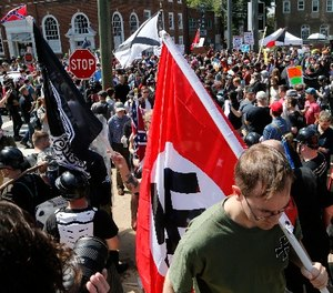 This Saturday, Aug. 12, 2017 image shows s white supremacist carrying a NAZI flag into the entrance to Emancipation Park in Charlottesville, Va.