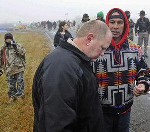 In this Oct. 26, 2016 file photo, Morton County Sheriff Kyle Kirchmeier, front, listens to Brian Wesley Horinek, of Oklahoma, outside the New Camp on Pipeline Easement in North Dakota. (Tom Stromme/The Bismarck Tribune via AP File)