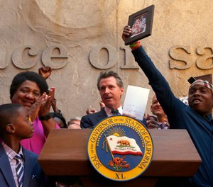 Gov. Gavin Newsom holds up the measure by Assemblywoman Shirley Weber, D-San Diego, left, that he signed that limits the use of lethal force by law enforcement Sacramento, Calif., Monday, Aug. 19, 2019. (AP Photo/Rich Pedroncelli)