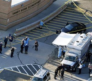 This Dec. 14, 2012 aerial file photo shows officials standing outside of Sandy Hook Elementary School in Newtown, Conn.