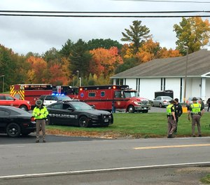 In this photo provided by WMUR-TV, police stand outside the New England Pentecostal Church after reports of a shooting on Saturday, Oct. 12, 2019, in Pelham, N.H. (Siobhan Lopez/WMUR-TV via AP)