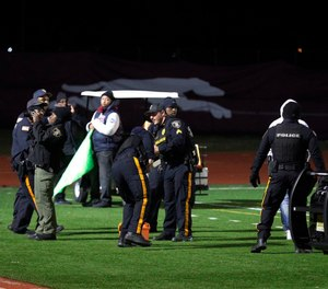 Police investigate the scene after a gunman shot into a crowd of people during a football game at Pleasantville High School in Pleasantville, N.J. (Photo/AP)