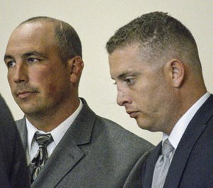 In this Aug. 18, 2015 file photo, former Albuquerque Police Detective Keith Sandy, left, and Officer Dominique Perez speak with attorneys during a preliminary hearing in Albuquerque, N.M.