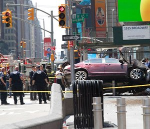 A car rests on a security barrier in New York's Times Square after driving through a crowd of pedestrians. (AP Photo/Mary Altaffer)