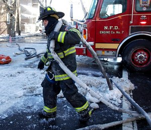 A Newark firefighter pulls a hose back onto an engine after helping battle a five building fire in Newark, N.J. (AP Photo/Julio Cortez)