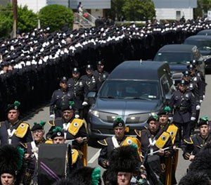 Police officers salute as the procession for police officer Brian Moore passes after his funeral mass, Friday.