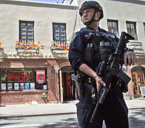 In this June 12, 2016 file photo, an armed police officer stands guard outside the Stonewall Inn, in New York after a Florida gunman's attack at a gay nightclub spread fear of more attacks. (AP Photo/Mary Altaffer, File)