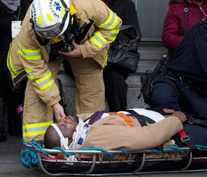 An injured passenger is assisted by an EMS worker as he lies on a gurney outside Atlantic Terminal after a Long Island Rail Road incident, Wednesday, Jan. 4, 2017, in the Brooklyn borough of New York. (AP Photo/Mark Lennihan)