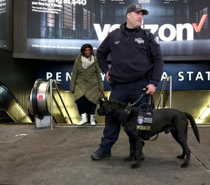 NYPD Counterterrorism Officer Frisna and his dog stand outside Penn Station in Manhattan. Under a proposed federal budget measure, the VIPR teams currently patroling many major transit hubs will be eliminated. (Photo/TNS)