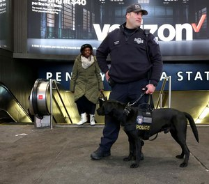 NYPD Counterterrorism Officer Frisna and his dog stand outside Penn Station in Manhattan. Under a proposed federal budget measure, the VIPR teams currently patroling many major transit hubs will be eliminated.