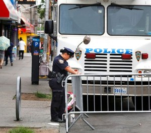 A police officer works near the site where an officer was killed in the Bronx section of New York, Thursday, July 6, 2017.