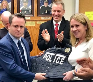 Leanne Simonsen, right, presents the first lightweight bulletproof vest to her late husband's partner, Det. Ricky Waters. (Photo/TNS)