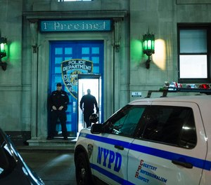 An NYPD officer stands outside the 1st Precinct in Tribeca where it is reported that approximately 30 officers have been diagnosed with COVID-19.