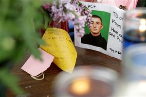 A picture of Brian Moore is displayed amongst flowers and candles at a memorial in front of his precinct house in the Queens section of New York, Tuesday, May 5, 2015. (AP Image)