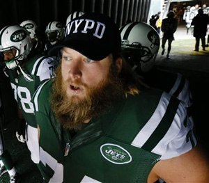 New York Jets center Nick Mangold (74) wears an NYPD hat as he waits to go on the field for the start of an NFL football game against the New England Patriots, Sunday, Dec. 21, 2014, in East Rutherford, N.J.