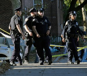Emergency personnel walk near the scene of a fatal shooting of a New York City police officer in the Bronx borough of New York, Sunday, Sept. 29, 2019.