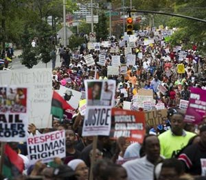 Demonstrators march to protest the death of Eric Garner, Saturday, Aug. 23, 2014, in the Staten Island borough of New York.