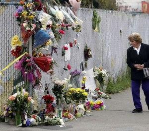A woman walks past a makeshift memorial near the site of a warehouse fire Monday, Dec. 5, 2016, in Oakland, Calif. (AP Photo/Marcio Jose Sanchez)