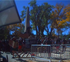 This still from bodycam video shows a crowd surrounding a war monument in Santa Fe during an Indigenous People's Day demonstration on October 12, 2020. (Photo/Santa Fe Police Department)