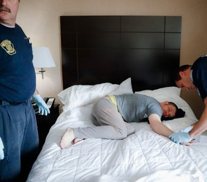 In this Nov. 2, 2017, file photo, Cincinnati police officers, firefighters and medics respond to a possible overdose report at a hotel in downtown Cincinnati.