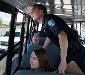 "Eagan police officer Luke Nelson strained to get a better look at an offender as he and fellow officers rode a school bus looking for distracted driversduring Wednesday's ""Busted by the Bus"" initiative. (Photo / MCT)"