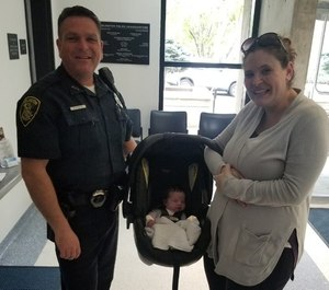Officer Brandon Kindle with Audra KcKinnon and baby Maeve