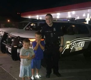 Officer Anthony Dia poses for a photo with two boys after showing off his cruiser just hours before he was fatally shot on July 3, 2020. (Photo/Toledo Police Department)