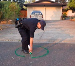 Oakland Police officer Anh Nguyen spray paints the street to mark that a house in Calistoga, Calif., is vacant on Wednesday, Oct. 11, 2017. (Paul Kitagaki Jr./The Sacramento Bee via AP)