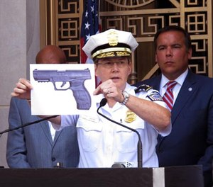 In this Thursday, Sept. 15, 2016, file photo, Columbus, Ohio, Police Chief Kim Jacobs displays a photo of the type of BB gun police say Tyre King pulled from his waistband before he was shot and killed by a police officer investigating an armed robbery report, during a news conference in Columbus, Ohio.