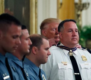 President Donald Trump presents the Medal of Valor to Dayton Police officer Sgt. William Knight, one of six Dayton police officers in the East Room of the White House in Washington, Monday, Sept. 9, 2019, for stopping a mass shooter in August in Dayton, Ohio. (AP Photo/Alex Brandon)