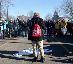 Alanna Galloway speaks to a crowd in front of a police precinct Saturday, Nov. 21, 2015, in Minneapolis.